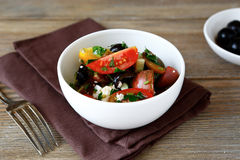 Salad with tomatoes, olives and cheese in a white bowl Stock Photos