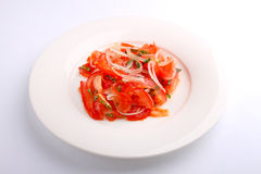 Salad with tomatoes and onion in a white plate Stock Photo