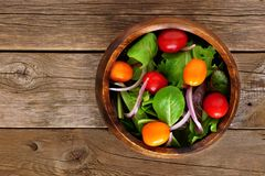 Salad with tomatoes and onions over rustic wood Royalty Free Stock Images