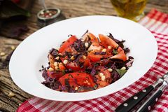 Salad from tomatoes with a violet basil and pine nuts. Stock Photo