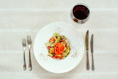 Salad with turkey pepper mushrooms, cornichots and vegetables, in a white plate on a light background, cutlery and red wine, table stock photography