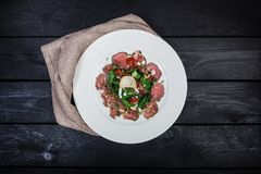 Salad of veal with milk sauce and spinach stock image