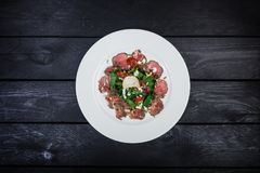 Salad of veal with milk sauce and spinach stock photo
