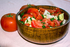 Salad. Vegetable salad in a wooden bowl.greens, tomatoes,onions and cucumbers in a salad bowl Royalty Free Stock Photography