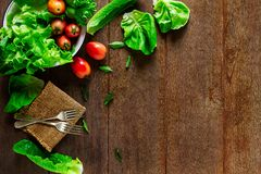 Salad vegetables in bowl with forks on vintage grunge wooden table Stock Image