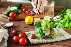 Salad of vegetables in a deep bowl of glass. Arugula, lettuce, radishes, onions, cherry tomatoes. In the background male hand sliced onions on cutting board Stock Photos