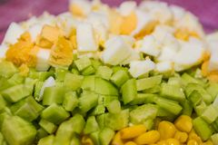 The salad of corn, eggs, fresh cucumber an fresh kiwi. The salad of vegetables and eggs Stock Photo