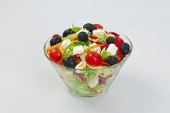 Salad with vegetables. In glass bowl , made from olives, cheese, tomatoes, pepper, lettuce, carrots Stock Photography