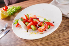 Salad with vegetables and greens. Greek salad on the white plate with greens and cheese Stock Images