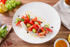 Salad with vegetables and greens. Greek salad on the white plate with greens and cheese Stock Image