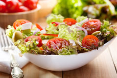 Salad with vegetables and greens on wooden table Stock Image