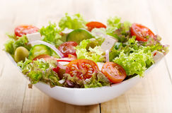 Salad with vegetables and greens on wooden table Royalty Free Stock Photos