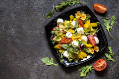 Salad with vegetables and pasta on a black plate Stock Photos