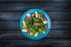 Salad with vegetables and tuna steak on a beautiful blue plate. Colored wooden background. Top view royalty free stock photos