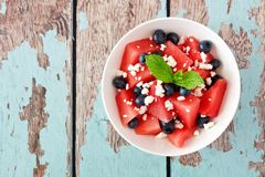 Salad with watermelon, blueberries and feta, above over rustic blue wood. Summer salad with watermelon, blueberries and feta cheese, above view on a rustic blue Stock Image