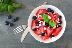 Salad with watermelon, blueberries and feta, above scene on stone. Summer salad with watermelon, blueberries and feta cheese, overhead scene on a dark stone Royalty Free Stock Photography