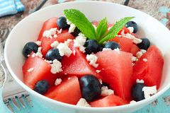Salad with watermelon, blueberries and feta, cheese close up. Summer salad with watermelon, blueberries and feta cheese close up in a white bowl Royalty Free Stock Photo