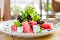 Salad with watermelon and herbs, on a white plate, on a wooden background, side view stock image