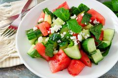 Salad with watermelon, mint, cucumber and feta, close up. Summer salad with watermelon, mint, cucumber and feta cheese close up in a white plate Royalty Free Stock Image