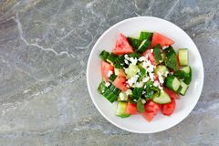 Salad with watermelon, mint, cucumber and feta, on dark stone. Summer salad with watermelon, mint, cucumber and feta cheese, above view on a dark stone Stock Photo