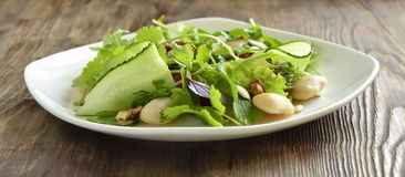 Salad with white beans, greens, cucumbers and sweet peppers Stock Photo