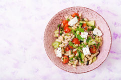 Salad of white beans, tomato, celery, cucumber, arugula, red onion and feta cheese in bowl. Stock Photography