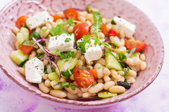 Salad of white beans, tomato, celery, cucumber, arugula, red onion and feta cheese in bowl Royalty Free Stock Photos