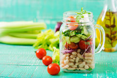 Salad of white beans, tomato, celery, cucumber, arugula, red onion and feta cheese in a jar. Stock Photo