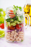 Salad of white beans, tomato, celery, cucumber, arugula, red onion and feta cheese in a jar. Stock Photos