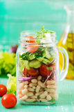 Salad of white beans, tomato, celery, cucumber, arugula, red onion and feta cheese in a jar. Royalty Free Stock Image