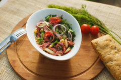 Salad in white bowl on a background of nature Royalty Free Stock Photo
