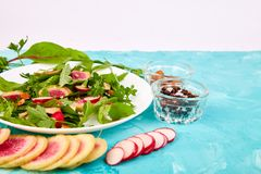 Salad in white plate around Ingredient. Mix leaf radish,lettuce, mangold, parsley,  arugula, almond, salt, tasty, balsamic, pepper. Healthy diet Clear food Stock Photography