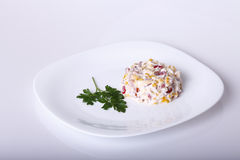 Salad on a white plate. On light background Royalty Free Stock Photography