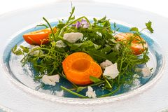Salad with wild herbs goat chees and roasted apricots. On glass plate royalty free stock photo