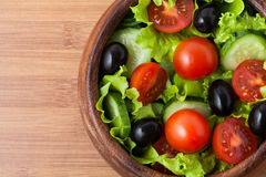 Salad on wooden plate. Stock Photos