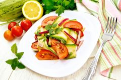 Salad with zucchini and tomato in plate on light board Royalty Free Stock Image