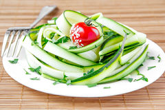 Salad from the zucchini ribbons, tomato and parsley. On white plate Stock Image