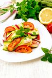 Salad with zucchini and tomato in plate on board Royalty Free Stock Photography