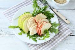 Salada clara com maçãs, aipo e rúcula em uma placa Fotos de Stock