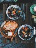 Salada colorida saudável do vegetariano e pão caseiro em uma tabela de madeira do vintage com flores imagens de stock