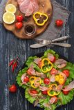 A salada com bacon e os legumes frescos é servida em uma placa Fundo preto de madeira, vista superior Fotografia de Stock Royalty Free