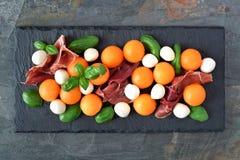 Salada com cantalupo, mussarela, prosciutto e manjericão no servidor da ardósia Fotografia de Stock Royalty Free