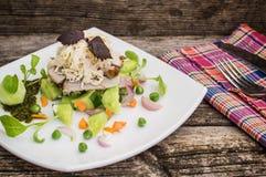 Salada com carne cozida desbastada, puré derretido do queijo, do pepino, da cenoura e da ervilha Fundo de madeira Close-up fotos de stock