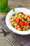 Salada com grãos-de-bico e tomates em uma bacia Imagens de Stock