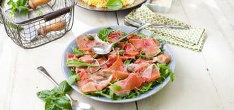 Salada com jamon, tomates e rúcula do presunto de parma na placa foto de stock