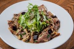 A salada com língua pôs de conserva cogumelos e o abobrinha polvilhou a sagacidade Foto de Stock Royalty Free