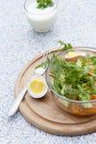 Salada com legumes frescos e ervas em uma bacia de vidro em uma placa de madeira, em ovos cozidos e em yogur Fotos de Stock