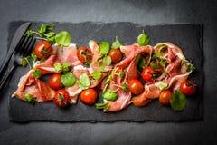 Salada com o serrano do jamon do presunto, tomates de cereja, rúcula, placa da ardósia Fotografia de Stock Royalty Free