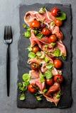 Salada com o serrano do jamon do presunto, tomates de cereja, rúcula, placa da ardósia fotografia de stock
