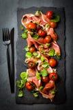 Salada com o serrano do jamon do presunto, tomates de cereja, rúcula, placa da ardósia Foto de Stock Royalty Free